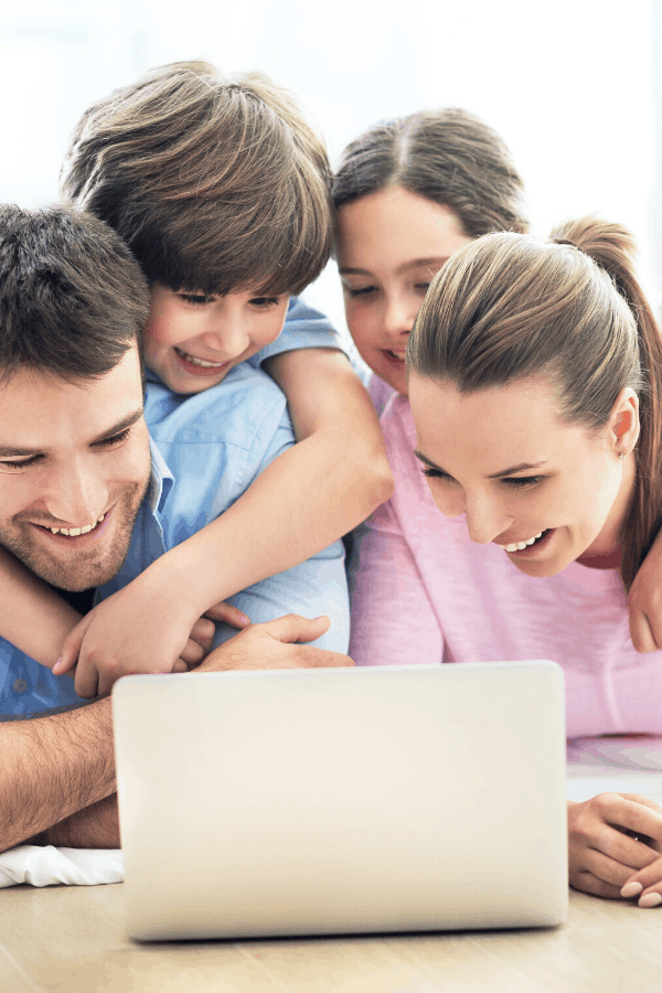 family crowded around a laptop